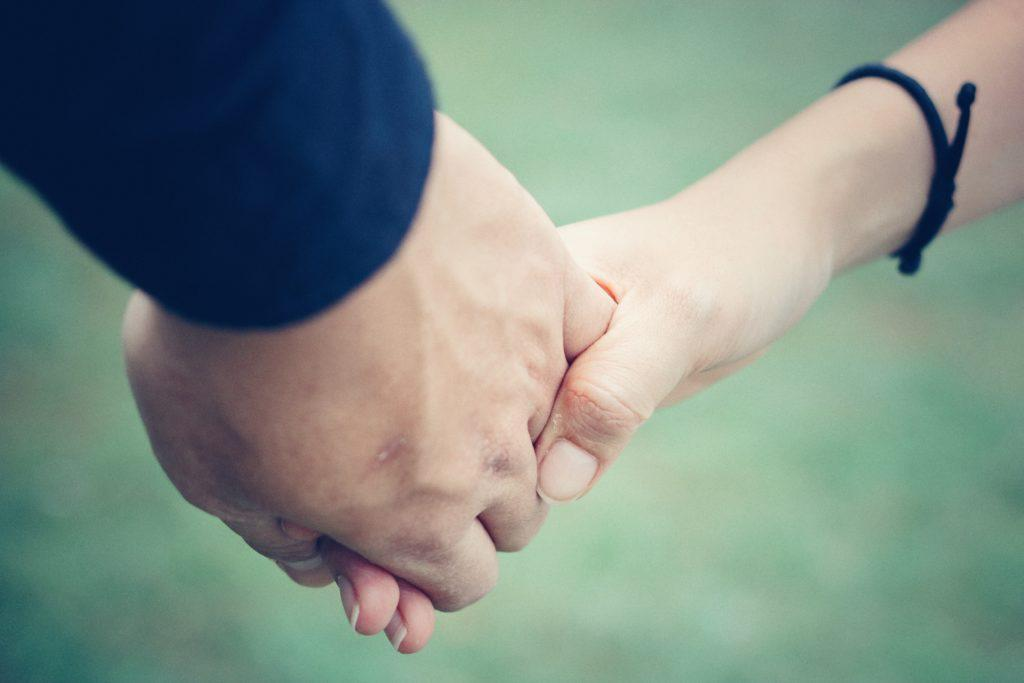 Two people hold each other's hand.